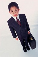Portrait of a boy dressed as a businessman holding a briefcase