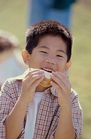 Portrait of a boy biting into a sandwich
