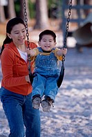 Mother pushing her son on a swing
