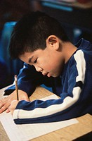 Boy writing on a paper with a pencil
