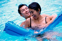 Young couple enjoying in a swimming pool