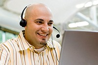 Close-up of a male customer service representative wearing a headset sitting in front of a laptop
