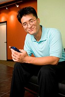 Portrait of a businessman sitting in an office holding a mobile phone