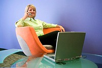 Portrait of a businesswoman sitting in front of a laptop talking on a mobile phone