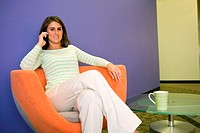 Businesswoman sitting on a chair talking on a mobile phone