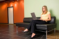 Businesswoman sitting on a couch working on a laptop