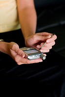 Mid section view of a businesswoman working on a palmtop