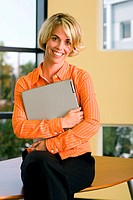 Portrait of a businesswoman sitting on a desk holding a laptop