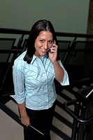 Portrait of a businesswoman standing on stairs talking in a mobile phone