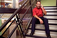 Portrait of a businessman sitting on stairs talking on a mobile phone