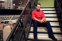 Businessman sitting on stairs holding a mobile phone
