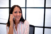 Portrait of a businesswoman sitting in an office talking on a mobile phone
