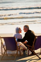 Senior couple sitting on deck chairs on the beach