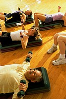 Group of people exercising in a step aerobics class