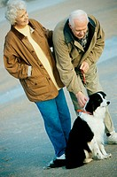 Senior couple standing with their dog on the beach (thumbnail)