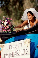 Bride preparing to toss a bouquet of flowers from a convertible car