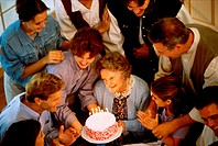 High angle view of a family in front of a birthday cake