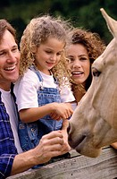 Parents with their daughter standing in front of a horse