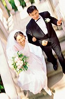 High angle view of a newlywed couple walking down stairs