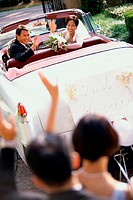 High angle view of a newlywed couple waving from a convertible car