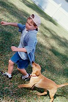 Side profile of a boy playing with his dog