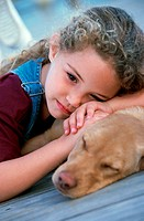 Close-up of a girl lying with her dog