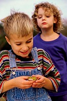 Boy standing with his friend holding a frog