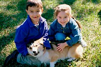High angle view of a boy and a girl petting their dog