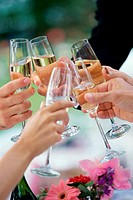 Close-up of peoples hands toasting with glasses of champagne