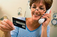 Mid adult woman talking on a cordless phone holding a credit card