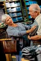 Senior woman holding a t-shirt against a senior man in a clothing store