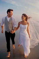 Newlywed couple holding hands running on the beach