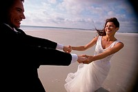 Newlywed couple spinning each other on the beach