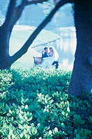 Newlywed couple sitting on a park bench