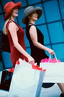 Side profile of two young women carrying shopping bags