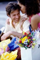 Young couple sitting on the sidewalk with shopping bags