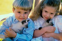 Portrait of a boy and a girl sitting with Siamese kittens