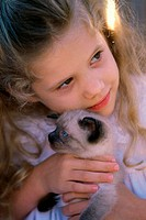 Close-up of a girl holding a Siamese kitten