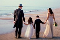 Rear view of a newlywed couple walking on the beach with a flower girl and a ring bearer