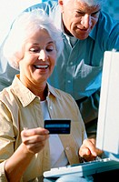 Senior couple in front of a computer holding a credit card