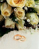 Close-up of wedding rings with a bouquet of flowers