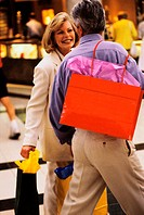 Mature couple walking with shopping bags
