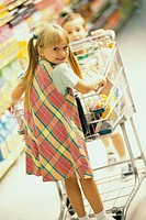 Girl and a boy playing with a shopping cart in a supermarket