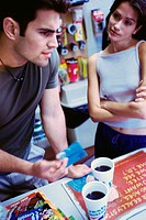 Young couple standing at a store counter holding a credit card