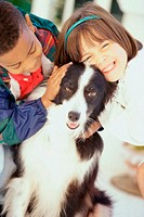 Portrait of a girl and a boy petting a dog