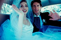 Newlywed couple waving from inside a car