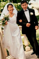 Portrait of a newlywed couple walking arm in arm