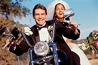 Portrait of a newlywed couple riding on a motorcycle