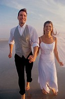 Newlywed couple walking on the beach