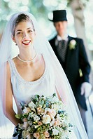 Portrait of a bride with her groom standing behind her